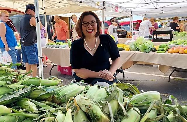 Smiling woman in front of sweet corn at farmers market